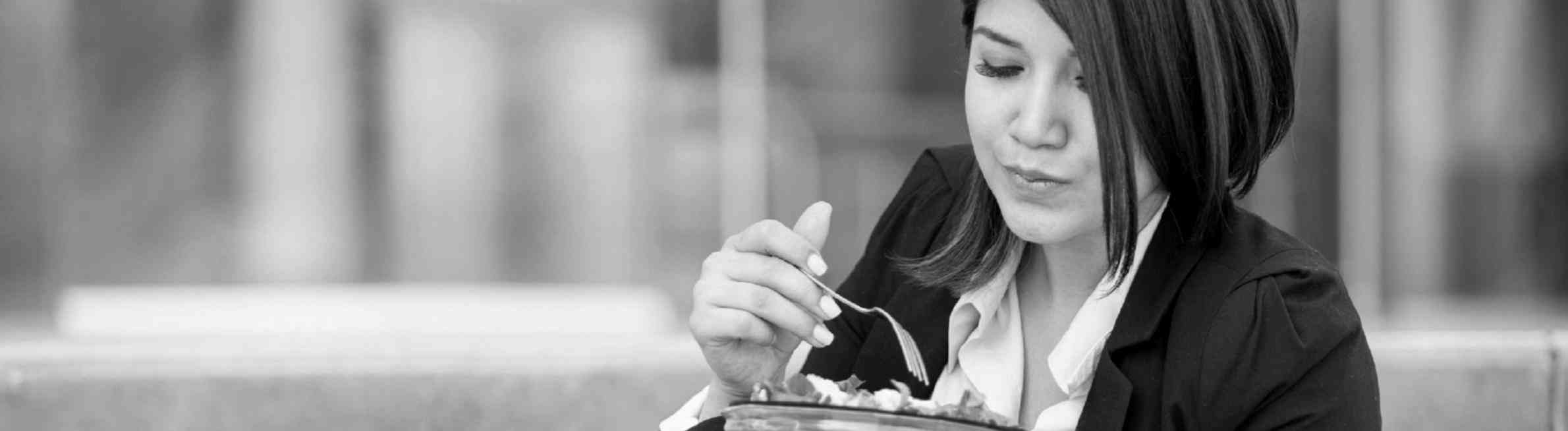 Woman eating to manage her stress after attending Workplace Learning Solutions eating plan for stress management webinar